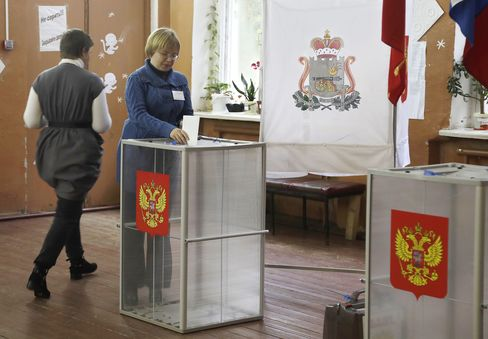 A woman casts her ballot at a polling station near Smolensk on Sept. 18.