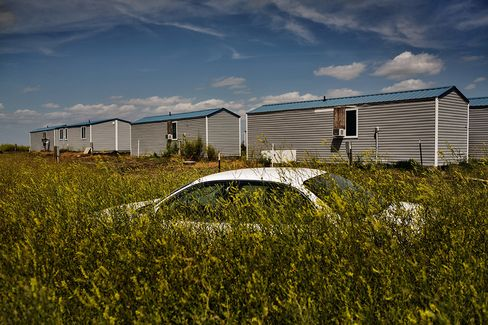 A car in the process of being swallowed by the prairie at a man camp outside Williston, N.D., on July 24, 2014.