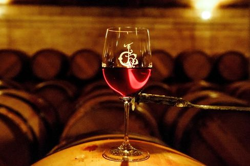 A glass of red wine stands on an oak barrel in the cellar of Château Haut-Brion in Pessac-Léognan.
