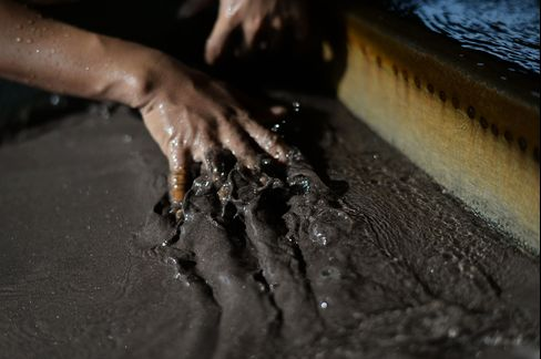 A worker runs his hand through a slurry of tin ore on Bangka island, Indonesia. Photographer: Dimas Ardian/Bloomberg