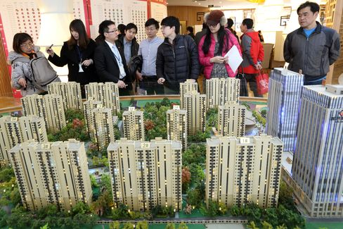 Visitors look at a model of an apartment complex in a showroom in Beijing
