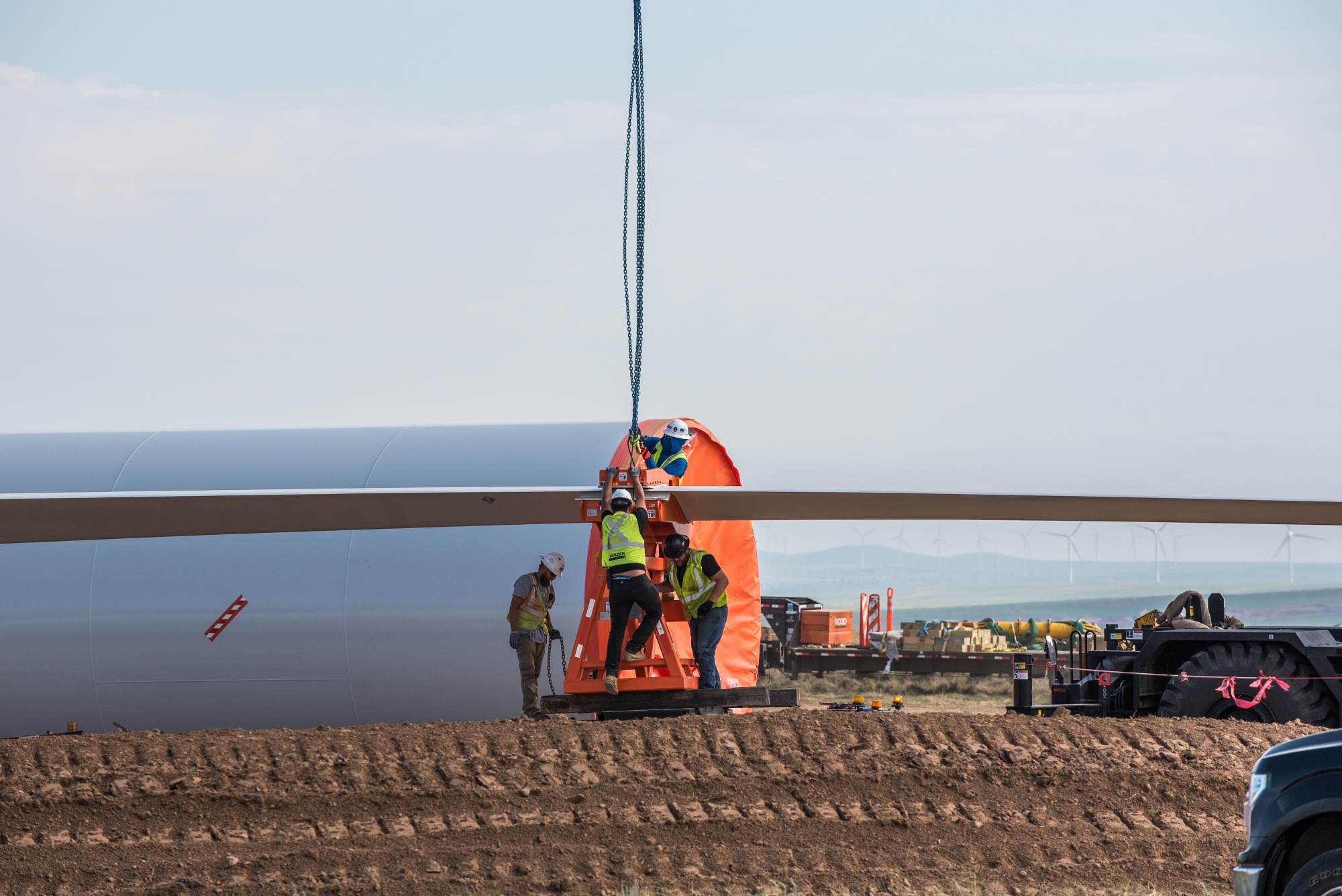 Construction workers unload a turbine blade at a wind farm in Encino, New Mexico.