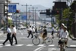 Pedestrians and cyclists cross a road in Matsue, Shimane Prefecture.
