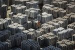 A worker stands among bundles of aluminum ingots sitting stacked at a stockyard in Wuxi, China.
