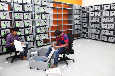 Employees arrange wardrobe into boxes during Myntra's bureau in Bangalore.