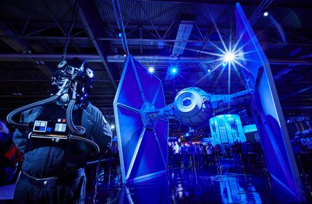 BIRMINGHAM, ENGLAND - SEPTEMBER 25:  A TIE Pilot stands in front of a life size model of a TIE Fighter from the film Star Wars, on September 26, 2015 in Birmingham, England. The UK Gaming Industry contributed more than ?1 billion to the UK's GDP in 2013 and estimates now put it's worth at  nearer ?1.72 billion.  (Photo by M Bowles/Getty Images)