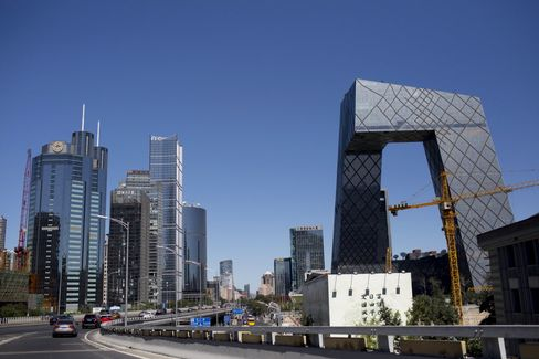 Traffic passes the China Central Television (CCTV) headquarters, right, and other commercial buildings in the central business district inBeijing, China.