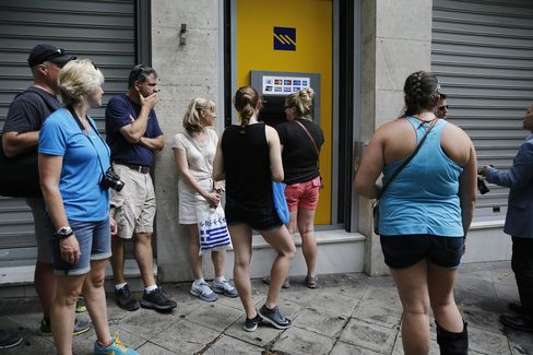 People wait in line at an ATM at a Piraeus Bank branch in Athens