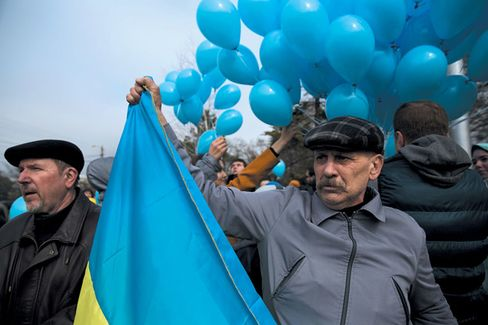A man holds a Ukrainian flag at a pro-Ukraine rally in Simferopol, Crimea, on Sunday. The national colors are a rare sight in Crimea these days