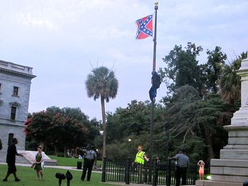 Police surround the flagpole flying the Confederate battle flag at a monument at the statehouse in Columbia, S.C., on Saturday as Newsome climbs the pole to remove the banner.