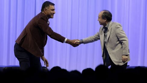 Billionaire Masayoshi Son, chairman and chief executive officer of SoftBank Group Corp., right, shakes hands with Nikesh Arora, president and chief operating officer of SoftBank Group Corp.