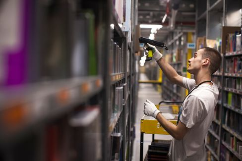 Amazon warehouse workers wear GPS tracking devices and are assigned products for collection by a hand-held scanner