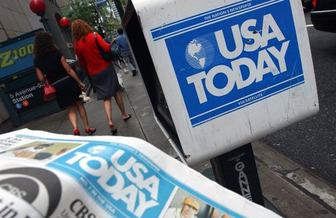 Pedestrians Walk Past a USA Today Honor Box in New York
