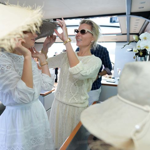 Nicky Tindill helps a guest work a style during a Jonathan Howard from Hatmaker private event aboard her father Sandy Oakley's yacht, Andiamo.