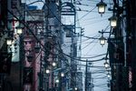 Power and utility cables hang from poles on a street in Hachioji in Tokyo.
