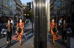 A shop window reflects pedestrians wearing protective face masks on New Bond Street in central London, U.K.