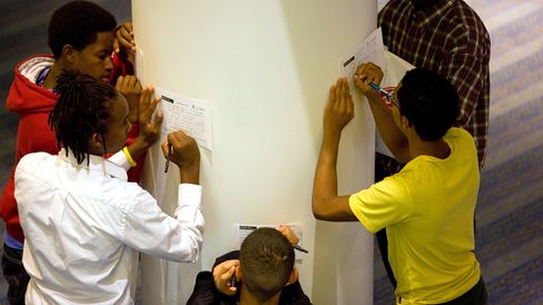 Teens fill out registration forms for a summer youth jobs and training expo in in Denver, Colorado.