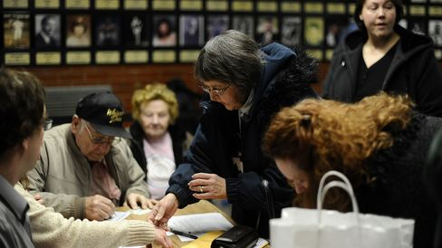 Voters register to cast their ballots during Republican caucuses at a school in Des Moines, Iowa, on Jan. 3, 2012.