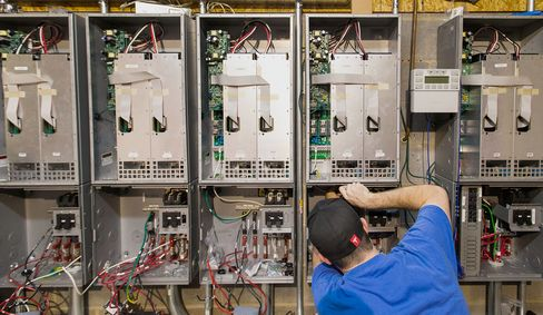 Day trader Jason Hughes works on running electrical wiring to junction boxes used to convert captured solar energy to store in Tesla Motors Inc. batteries in Hickory, North Carolina.