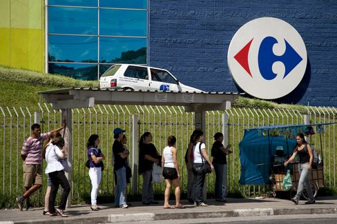 Patrons at a bus stop outside a Carrefour store in Brazil