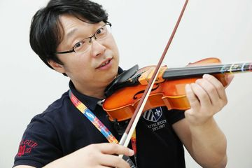 Chon Dae-Young, creative leader for JamIT device, developed by Samsung Electronics Co. Creative Lab (Samsung C- Lab), with a device attached to a violin.