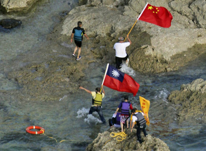 Pro-China activists carrying Chinese and Taiwanese national flags walk on the disputed islands known as 'Senkaku' in Japan and 'Diaoyu' in China after arriving by boat