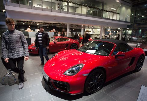 Visitors look at a Porsche Boxster luxury sports car for sale at a dealership in Moscow on Dec. 15
