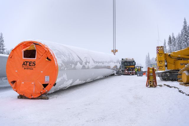 A crane winches a section of a wind turbine tower into place ahead of installation