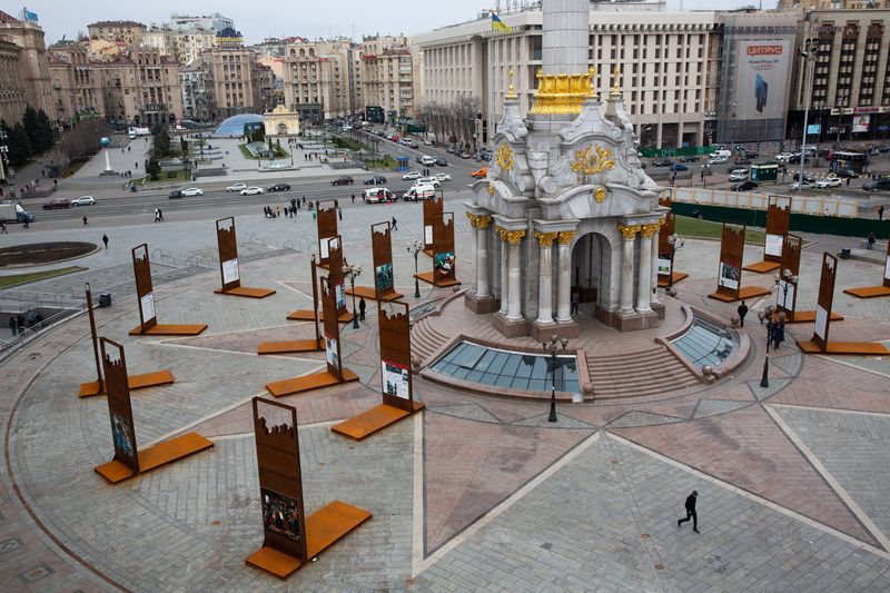 Pedestrians walk past the independence monument on Independence Square, also known as Maidan, in Kiev, Ukraine.