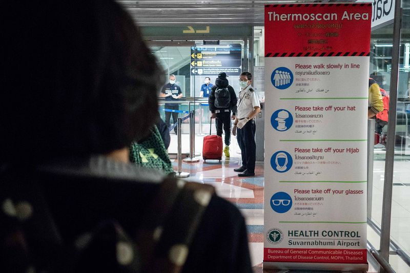 Public Health Officials run thermal scans on passengers in Bangkok on Jan. 8.