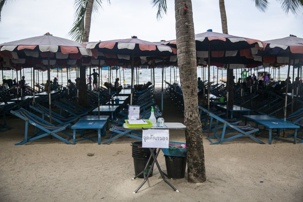 Hand sanitizer sits on a check-in table next to beach chairs and umbrellas at Bangsaen Beach in Chonburi, Thailand.