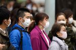 Pedestrians wearing protective masks wait to cross a road in the Ginza area in Tokyo, Japan.