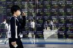 Pedestrians reflected in an electronic stock board outside a securities firm in Tokyo, Japan, on Thursday, Oct. 29, 2020.