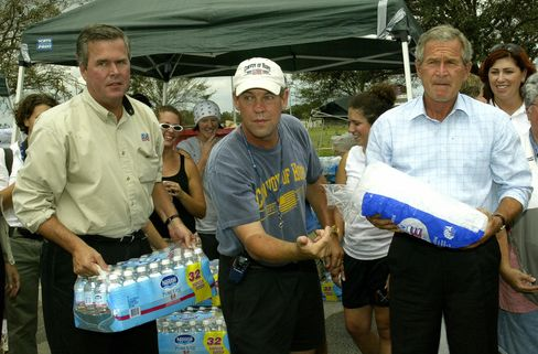 FT PIERCE, UNITED STATES:  US President George W. Bush(R) and his brother Florida Governor Jeb Bush(L) assist victims of Hurricane Frances 08 September 2004 at a government relief station in Ft. Pierce, Florida.  President Bush and Governor Bush passed out cases of water and ice to residents in need.    AFP Photo/Paul J. Richards  (Photo credit should read PAUL J.RICHARDS/AFP/Getty Images)