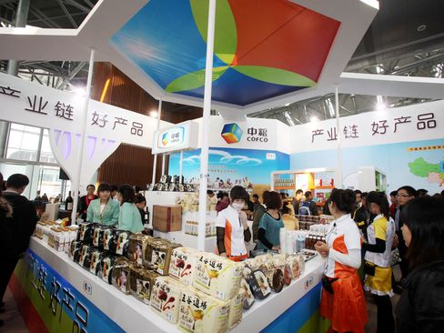 People visit a COFCO stand during an exhibition in Tianjin, China.