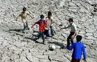 Indian boys play football on a dry bed p