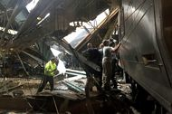 Train personnel survey the NJ Transit train that crashed in to the platform at the Hoboken Terminal on Sept. 29, in Hoboken.