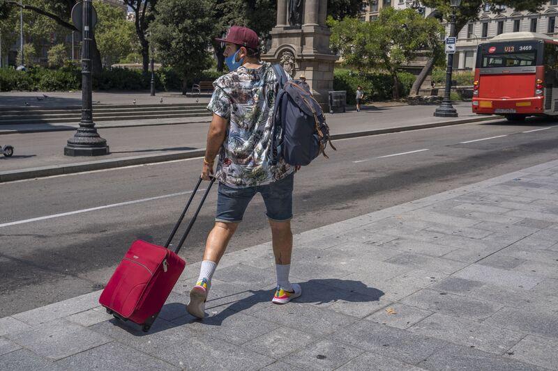 Una persona que lleva una maleta en la estación de Aero Bus con destino