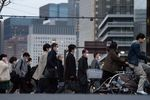Pedestrians wearing face masks cross a road in the Shinbashi district in Tokyo, Japan, on Monday, March 9, 2020.