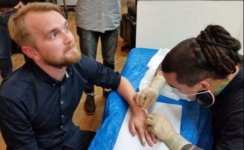 An employee at Epicenter has the NFC microchip implanted by a piercing specialist