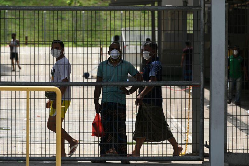 Công nhân nước ngoài nhìn ra từ hàng rào của Ký túc xá công nhân ở Singapore vào ngày 9 tháng 4. ( Roslan Rahman / AFP qua Getty Images)