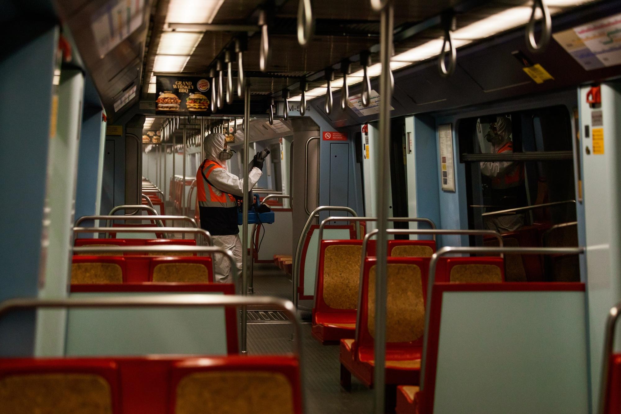 Seorang pekerja kota menyemprotkan desinfektan di bagian dalam gerbong kereta di sebuah stasiun di Lisbon pada 15 April.