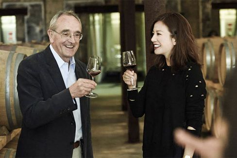 Famous wine consultant Jean-Claude Berrouet, who made Chateau Petrus for 47 years, shares a glass of red with film star Zhao Wei in the barrel room at Chateau Monlot. Wei purchased the chateau in 2011.