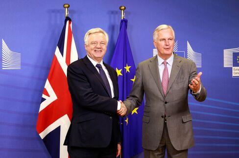 握手を交わすデービス英EU離脱担当相(左)とEU側交渉責任者のバルニエ氏(7月17日、ブリュッセル)