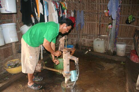 Nguyen Van Nhin pumps well water inside his home.