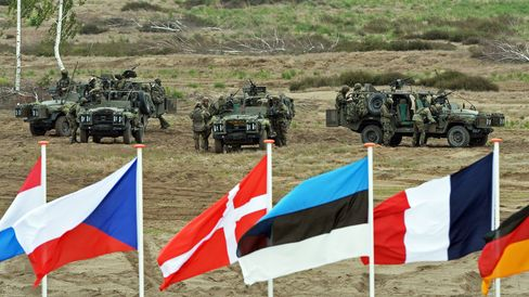 Soldiers prepare for a NATO Response Force (NRF) exercise behind flags of participating nations in Zagan, southwest Poland on June 18, 2015.