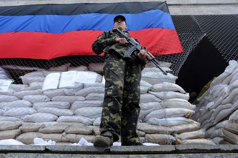 An Armed Man Stands Outside a Building in Slavyansk, Ukraine