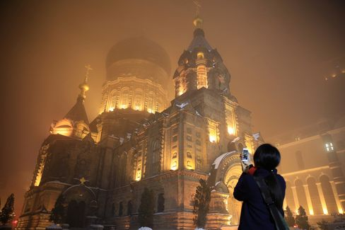 A woman take photos of the Saint Sophia Cathedral in Harbin on Nov. 10, 2015