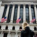 American flags fly as a pedestrian walks past the New York Stock Exchange (NYSE) in New York, U.S., on Friday, Feb. 23, 2018. U.S. stocks rose with Treasuries and the dollar slipped as investors await clues on Federal Reserve policy intentions under new Chairman Jerome Powell.
