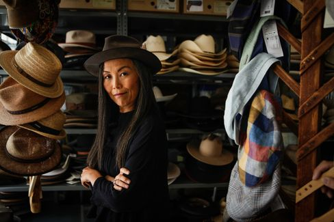 Chief Executive Officer Kajimoto stands in the back of her New York office amid an array of Stetson's many hat styles.